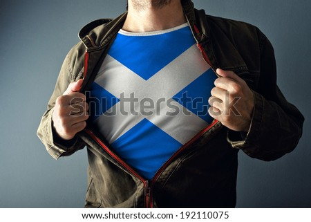 Man stretching jacket to reveal shirt with Scotland flag printed. Concept of patriotism and national team supporting. - stock photo