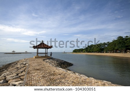 Man stretching next to a small gazebo at the Sanur Beach in Bali - stock photo