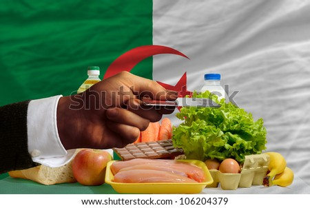 man stretching out credit card to buy food in front of complete wavy national flag of algeria - stock photo