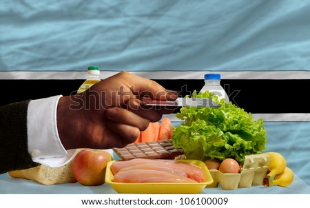 man stretching out credit card to buy food in front of complete wavy national flag of botswana - stock photo