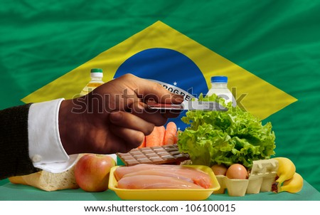 man stretching out credit card to buy food in front of complete wavy national flag of brazil - stock photo