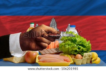 man stretching out credit card to buy food in front of complete wavy national flag of cambodia - stock photo