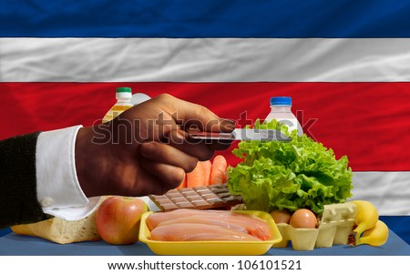 man stretching out credit card to buy food in front of complete wavy national flag of costarica - stock photo