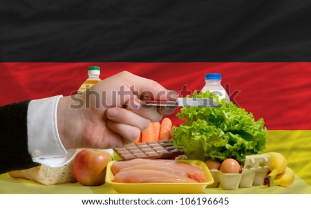 man stretching out credit card to buy food in front of complete wavy national flag of germany - stock photo