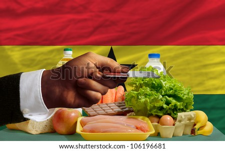man stretching out credit card to buy food in front of complete wavy national flag of ghana - stock photo