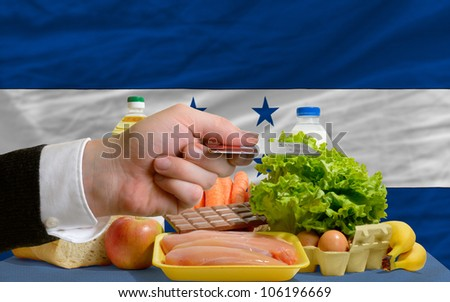 man stretching out credit card to buy food in front of complete wavy national flag of honduras - stock photo