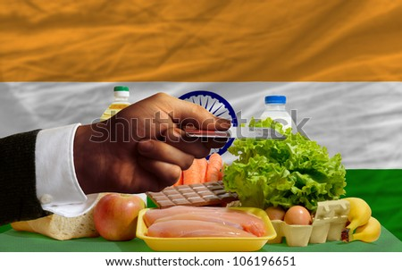 man stretching out credit card to buy food in front of complete wavy national flag of india - stock photo