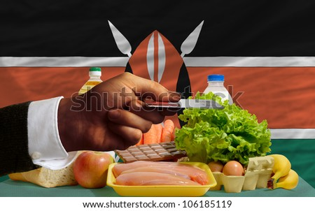 man stretching out credit card to buy food in front of complete wavy national flag of kenya - stock photo