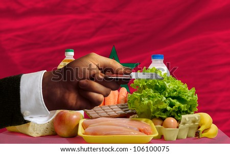 man stretching out credit card to buy food in front of complete wavy national flag of morocco - stock photo