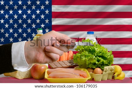 man stretching out credit card to buy food in front of complete wavy national flag of usa - stock photo