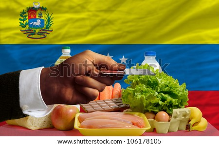 man stretching out credit card to buy food in front of complete wavy national flag of venezuela - stock photo