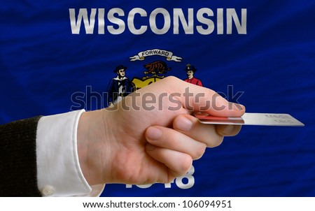 man stretching out credit card to buy goods in front of complete wavy national flag of american state of wisconsin - stock photo
