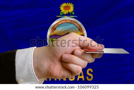 man stretching out credit card to buy goods in front of complete wavy national flag of american state of kansas - stock photo