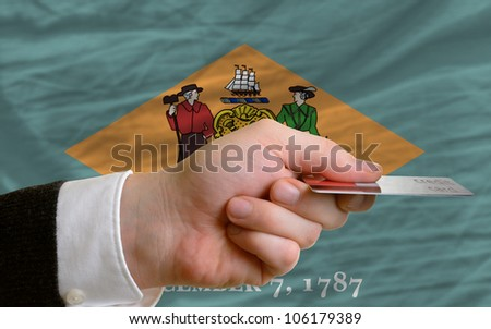 man stretching out credit card to buy goods in front of complete wavy national flag of american state of delaware - stock photo