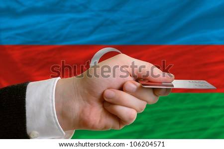 man stretching out credit card to buy goods in front of complete wavy national flag of azerbaijan - stock photo