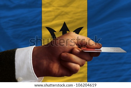 man stretching out credit card to buy goods in front of complete wavy national flag of barbados - stock photo