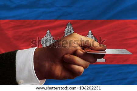 man stretching out credit card to buy goods in front of complete wavy national flag of cambodia - stock photo