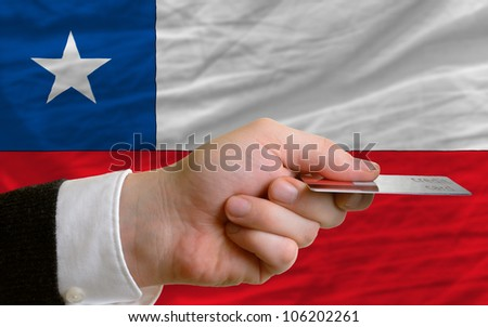 man stretching out credit card to buy goods in front of complete wavy national flag of chile - stock photo