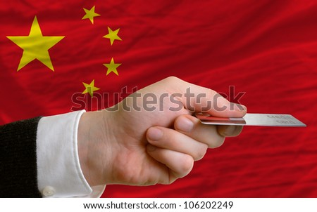 man stretching out credit card to buy goods in front of complete wavy national flag of china - stock photo
