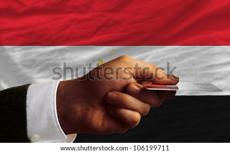 man stretching out credit card to buy goods in front of complete wavy national flag of egypt - stock photo