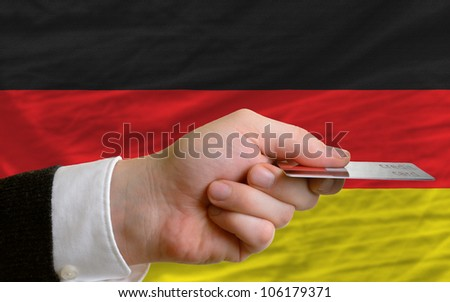 man stretching out credit card to buy goods in front of complete wavy national flag of germany - stock photo