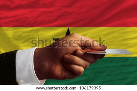 man stretching out credit card to buy goods in front of complete wavy national flag of ghana - stock photo