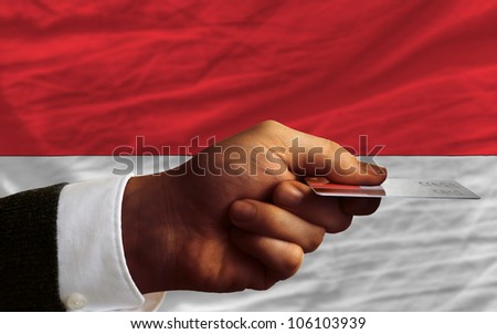 man stretching out credit card to buy goods in front of complete wavy national flag of indonesia - stock photo