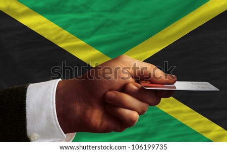 man stretching out credit card to buy goods in front of complete wavy national flag of jamaica - stock photo