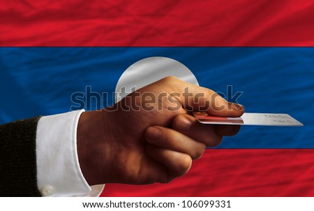 man stretching out credit card to buy goods in front of complete wavy national flag of laos - stock photo