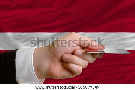 man stretching out credit card to buy goods in front of complete wavy national flag of latvia - stock photo