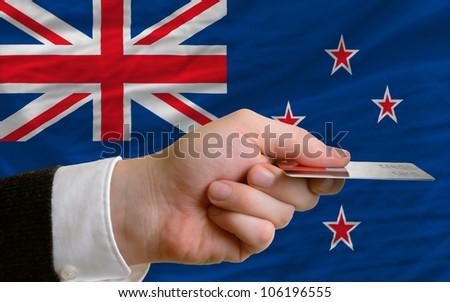 man stretching out credit card to buy goods in front of complete wavy national flag of new zealand - stock photo