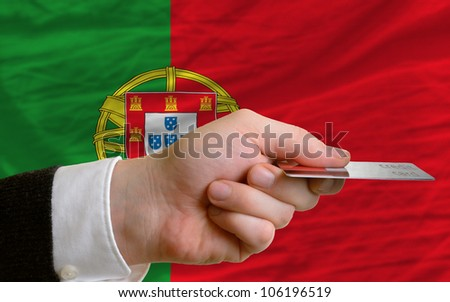 man stretching out credit card to buy goods in front of complete wavy national flag of portugal - stock photo