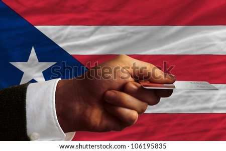 man stretching out credit card to buy goods in front of complete wavy national flag of puerto rico - stock photo