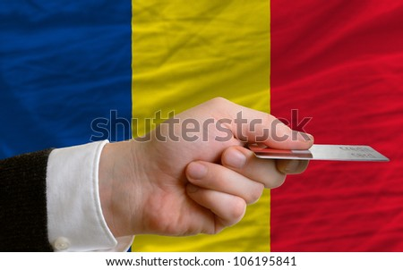 man stretching out credit card to buy goods in front of complete wavy national flag of romania - stock photo