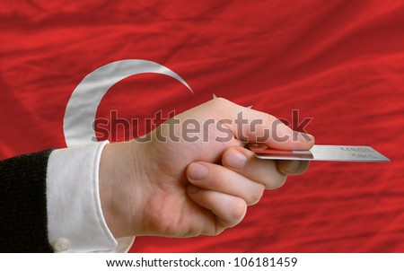 man stretching out credit card to buy goods in front of complete wavy national flag of turkey - stock photo