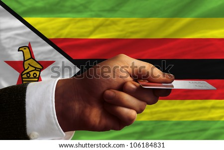 man stretching out credit card to buy goods in front of complete wavy national flag of zimbabwe - stock photo