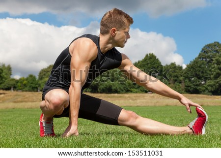 Man stretching out muscles in park - stock photo