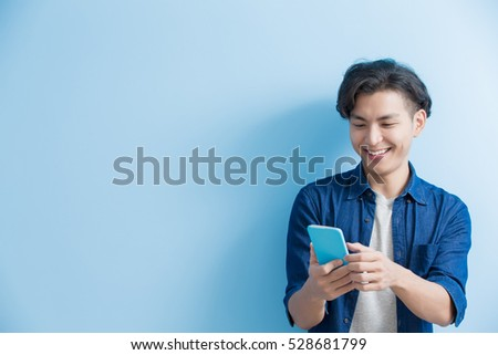 man student smile and use phone isolated on blue background,asian