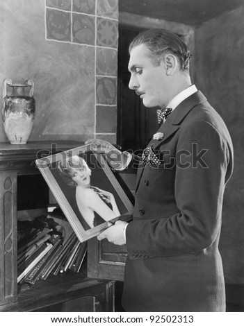 Man studying a picture of a woman