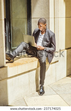 Man Studying Outside. Dressing in fashionable jacket, pants, leather shoes, wearing wristwatch, a young black student is sitting against a window frame, looking down, working on a laptop computer. - stock photo