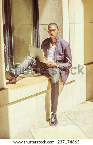 Man Studying Outside. Dressing in fashionable jacket, pants, leather shoes, wearing wristwatch, a young black student is sitting against window frame, reading, thinking, working on a laptop computer. - stock photo