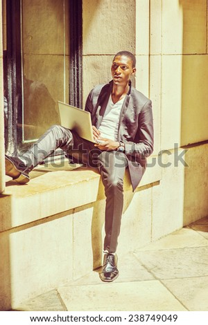 Man Studying Outside. Dressing in fashionable jacket, pants, leather shoes, wearing wristwatch, a young black student is sitting against a window frame, reading, thinking, working on laptop computer. - stock photo