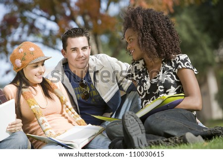 Man studying with two female friends at college campus