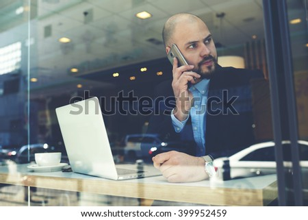 Man successful engineer is calling via cellphone to customer after receiving order by e-mail on laptop computer. Serious boss is talking on mobile phone, while is sitting with touch pad in coffee shop - stock photo