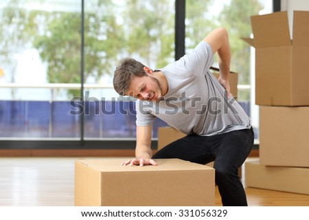 Man suffering back ache moving boxes in his new house - stock photo