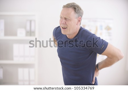 Man suffering from backache at office - stock photo