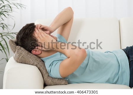 Man Suffering From Headache Lying On Sofa