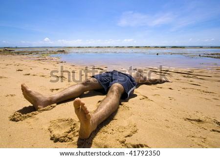 Man sunbathing in the tropical beach . - stock photo