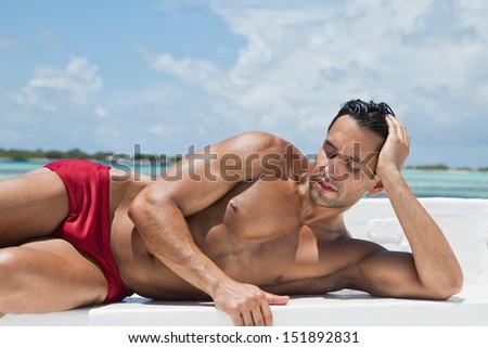 Man sunbathing on the beach - stock photo