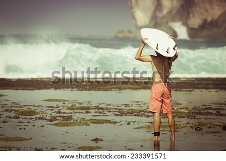 Man surfer with surfboard on a coastline. Bali, Indonesia - stock photo